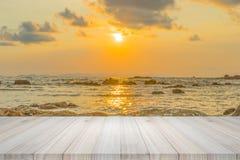 Leerer Holztisch oder Regalwand mit Sonnenuntergang oder Sonnenaufgang auf Sand Stockfotos