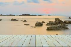 Leerer Holztisch oder Regalwand mit Sonnenuntergang oder Sonnenaufgang auf Sand Stockfoto