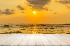 Leerer Holztisch oder Regalwand mit Sonnenuntergang oder Sonnenaufgang auf Sand Lizenzfreie Stockfotos