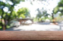 Leerer Holztisch vor abstraktem unscharfem Grün des Garten- und Haushintergrundes Für Montageproduktanzeige oder Entwurfsschlüsse stockfotografie