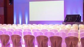 Leerer Innenraum des Luxuskonferenzsaales oder des Seminarraumes mit Projektorschirm und weißen Stühlen Stockfotografie