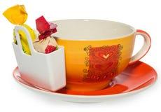 Leerer Kaffee, Teeschale mit Lagerung auf Süßigkeit mit zwei Bonbons Tasse und Untertasse verziert mit Herzen im Farbgelb, Orange Lizenzfreie Stockbilder