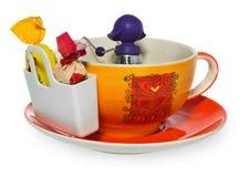 Leerer Kaffee, Teeschale mit purpurrotem silbernem infuser in Form eines Mädchens auf einer Kette und Lagerung auf Süßigkeit mit  Lizenzfreie Stockfotografie