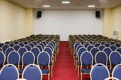 Leerer Konferenzsaal mit blauen Stühlen und rotem Teppich Lizenzfreie Stockfotografie