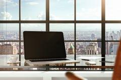Leerer Laptop auf einem Glastisch in den Ansichten eines modernen Büros und der Stadt Stockfoto