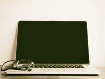 Leerer Laptop mit Brillen beim Weinlesetonen lizenzfreies stockfoto
