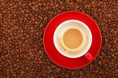 Leerer Latte in der roten Tasse und Untertasse auf Kaffeebohnen Lizenzfreie Stockfotos