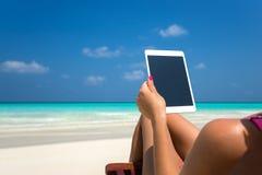 Leerer leerer Tablet-Computer in den Händen von Frauen auf dem Strand Stockfoto