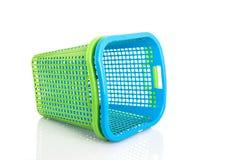 Leerer neuer blauer und grüner Plastikkorb lokalisiert auf Weiß Stockfotografie