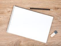 Leerer Notizblock, Bleistift und Radiergummi auf dem Holztisch Stockfotografie