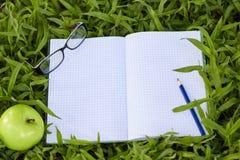Leerer Notizblock für Kopienraum auf grünem Gras Lizenzfreies Stockbild