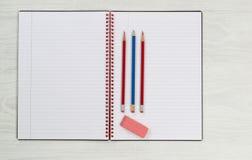 Leerer Notizblock mit Bleistiften und Radiergummi auf dem Desktop Stockfoto