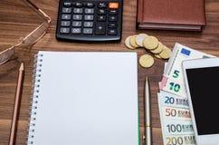 Leerer Notizblock mit Eurogeld, Mobile, Taschenrechner und Stift Stockbilder