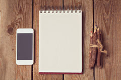 Leerer Notizblock mit intelligentem Telefon und Bleistiften auf Holztisch Lizenzfreies Stockbild