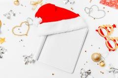 Leerer leerer Notizblock mit Sankt-Hut Weihnachtsgoldene Verzierungen O lizenzfreies stockfoto