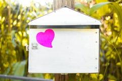 Leerer Notizblock oder klebriges Anmerkungsrosa auf Briefkasten mit Sonnenlichtba stockfoto