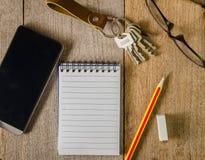 Leerer Notizblock, Schlüsselanhänger, Augengläser und Handy auf hölzernem Stockfotografie