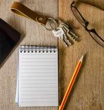 Leerer Notizblock, Schlüsselanhänger, Augengläser und Handy auf hölzernem Lizenzfreie Stockfotos