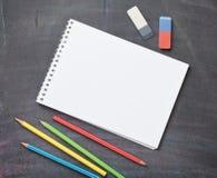 Leerer Notizblock und bunte Bleistifte auf Tafelhintergrund Stockbild