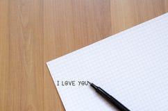 Leerer Notizbuch- und Tintenstift auf einem hölzernen Schreibtisch Stockfotografie