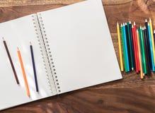 Leerer offener Sketchbook und farbige Bleistifte auf Holztisch stockbilder