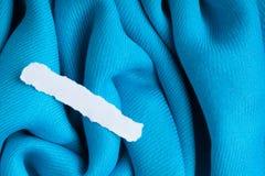 Leerer Papierfetzen auf Falten-Textilhintergrund des blauen Stoffes gewelltem Lizenzfreie Stockbilder