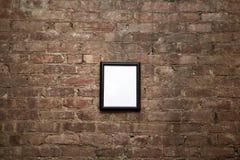 Leerer Rahmen auf Backsteinmauer Stockbild