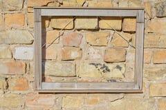 Leerer Rahmen auf gelber Backsteinmauer Stockbilder