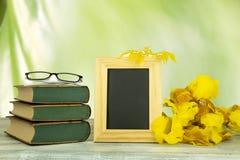 Leerer Rahmen mit einem Blumenstrauß von gelben Blumen und einem Paar Glas stockbilder