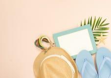 Leerer Rahmen und Sommerferieneinzelteile auf Cremehintergrund Strohhut, blaue Flipflops und hölzernes Armband Selektiver Fokus stockfotos