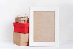 Leerer Rahmen und verschiedene Geschenkboxen auf der weißen Tabelle Stockbild