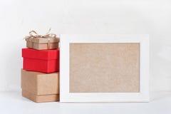 Leerer Rahmen und verschiedene Geschenkboxen auf der weißen Tabelle Stockfoto