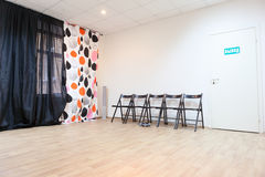 Leerer Raum mit Stühlen und Vorhängen auf Fenster Stockbild