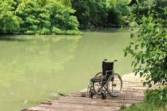 Leerer Rollstuhl auf einem hölzernen Pier Stockfotos