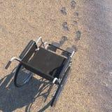 Leerer Rollstuhl auf einem Strand des Sandes mit Abdrücken Lizenzfreie Stockfotografie