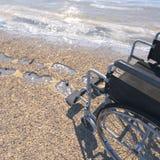 Leerer Rollstuhl auf einem Strand des Sandes mit Abdrücken Stockfoto