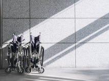 Leerer Rollstuhl auf Wand Hintergrund mit Schattenbeleuchtung Lizenzfreie Stockfotos