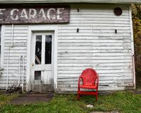 Leerer roter Metallstuhl nahe bei verlassenem Altbau Lizenzfreie Stockfotos