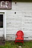 Leerer roter Metallstuhl nahe bei verlassenem Altbau Lizenzfreies Stockbild