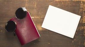 Leerer roter Pass und runde Sonnenbrille mit einer leeren Postkarte auf einem hölzernen Hintergrund Stockbild