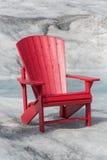 Leerer roter Stuhl, der auf Gletscher sitzt Stockbilder