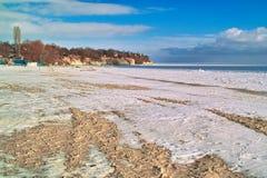 Leerer sandiger Strand abgedeckt mit Schnee Lizenzfreies Stockfoto