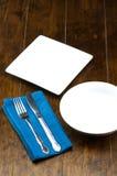 Leerer Schüssel- und Quadratteller mit Gabel, Messer, Napery auf hölzerner Tabelle Stockbild