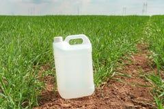 Leerer Sch?dlingsbek?mpfungsmittelkrug-Beh?lterspott oben auf wheatgrass Gebiet lizenzfreie stockfotografie