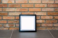 Leerer schwarzer Bilderrahmen auf der alten Backsteinmauer Stockbilder