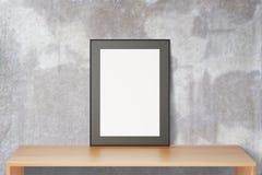 Leerer schwarzer Bilderrahmen auf Holztisch und Betonmauer, moc Stockfotos