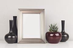 Leerer silberner Rahmen, auf einer weißen Tabelle mit Aloe und Vasen stockfotos