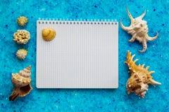 Leerer Sketchbook auf dem blauen Kristallhintergrund und den Muscheln lizenzfreies stockbild