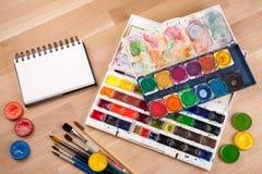 Leerer Sketchbook auf hölzerner Tabelle mit Kunstversorgungen herum Spott oben für Illustration oder Kunst Stockbild
