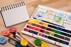 Leerer Sketchbook auf Kreidebrett mit Kunstversorgungen herum Spott oben für Illustration oder Kunst Lizenzfreie Stockfotos